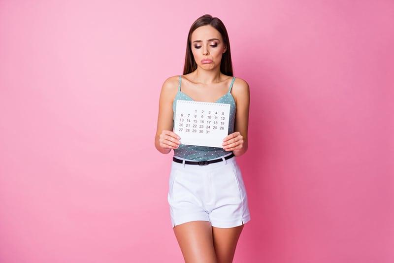 enttäuschte Frau, die einen Papierkalender hält und nach unten schaut