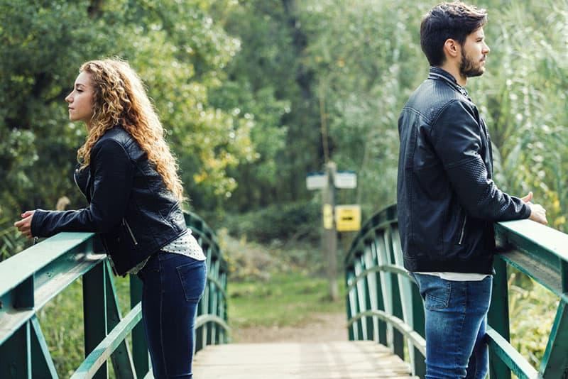 ernstes Paar, das auf der Brücke in der Natur auseinander steht