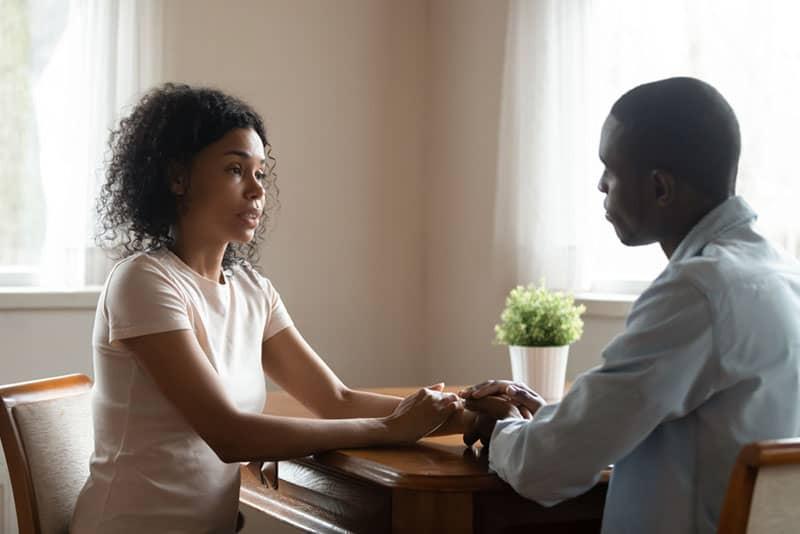 ernsthafte Frau, die mit Mann spricht, der seine Hände hält