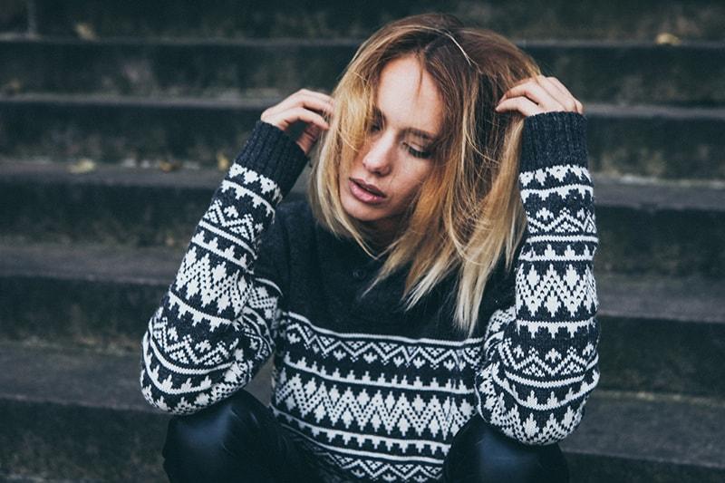 gestresste Frau sitzt auf der Treppe und berührt ihre Haare