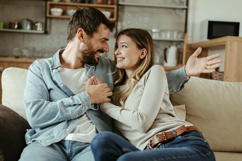 glückliches junges Paar, das auf der Couch sitzt