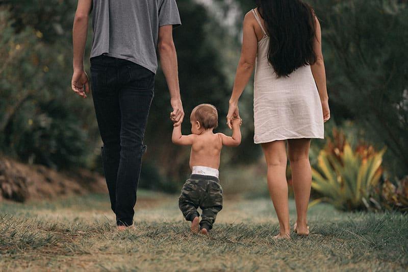 junge Eltern gehen mit Baby