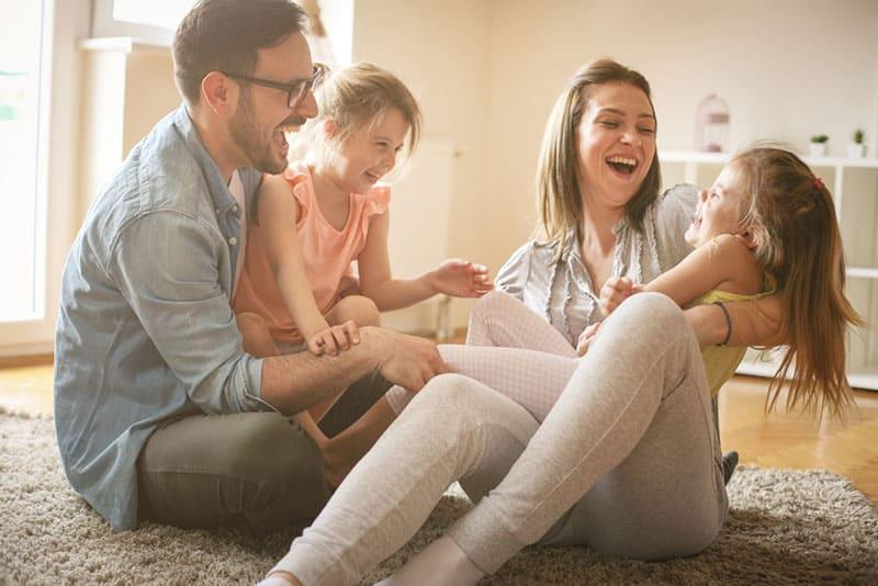 junge Eltern spielen mit ihren Kindern