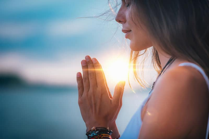 junge Frau, die im Freien betet