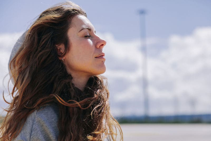 junge Frau, die tief im Freien atmet
