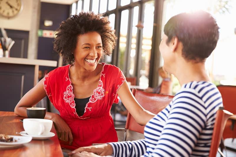 junge lächelnde Frau, die Freund im Café ansieht