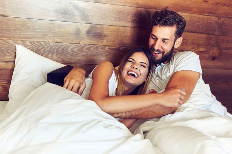 junger Mann, der Frau im Bett zum Lachen bringt