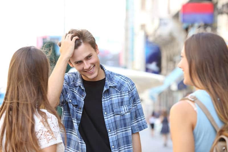 junger Mann flirtet mit zwei Frauen auf der Straße