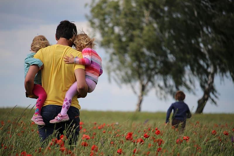 junger Vater, der Kinder auf dem Feld trägt