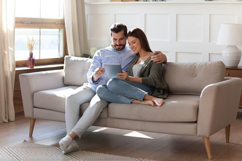 junges Paar sitzt auf der Couch und schaut am digitalen Computer zu