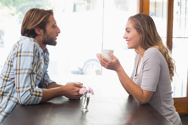 junges Paar spricht und trinkt Kaffee