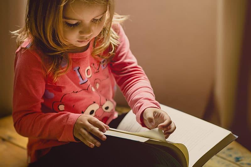 kleines Mädchen liest ein Buch