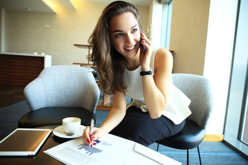 lächelnde Frau, die am Telefon arbeitet und spricht