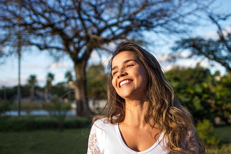lächelnde Frau, die im Park während des Tages steht