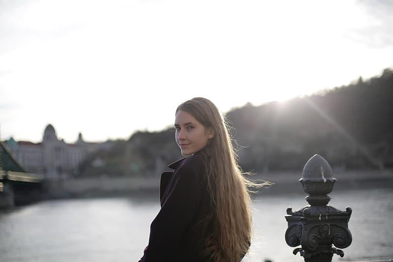 lächelnde Frau, die über den Rücken schaut, der nahe dem Fluss steht
