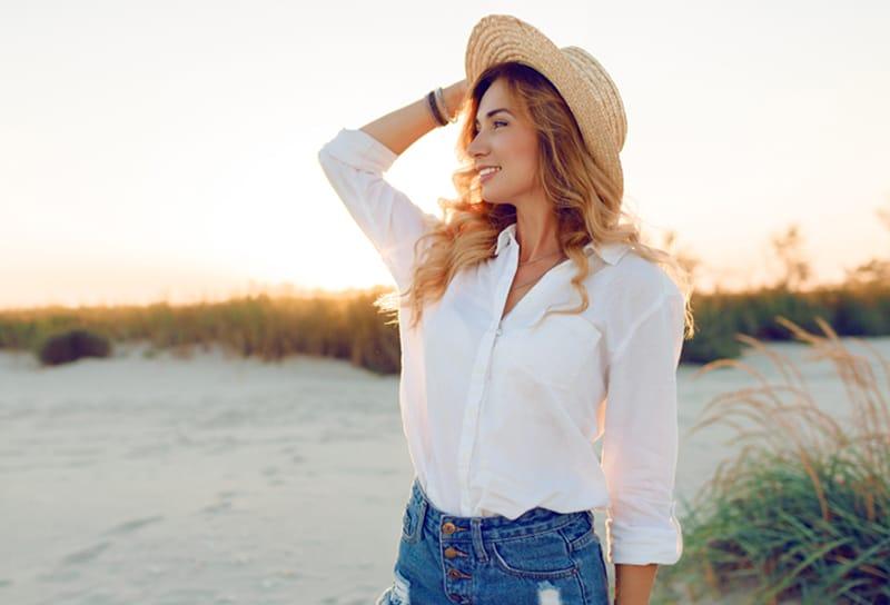 lächelnde Frau in der weißen Bluse und im Strohhut, die am Strand stehen