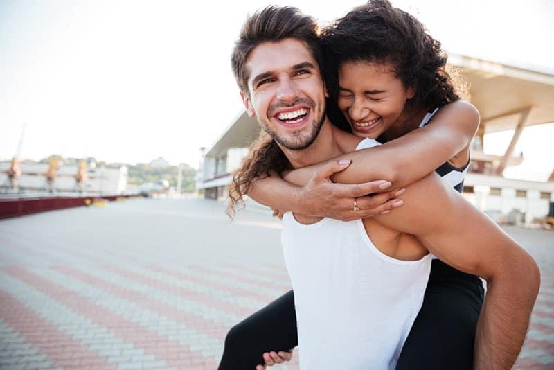 lächelnder Mann, der Frau auf seinem Rücken trägt