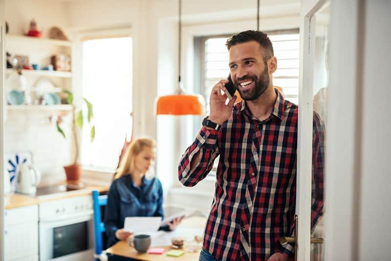 lächelnder Mann, der am Telefon spricht, während Frau arbeitet