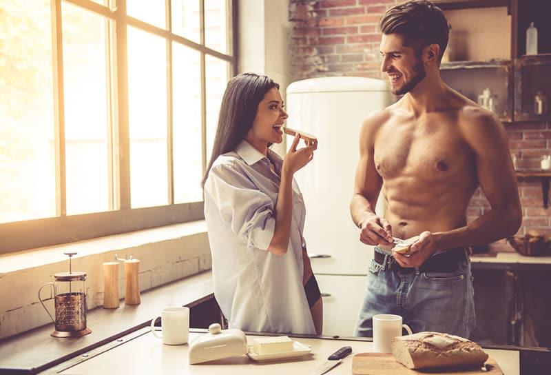 lächelndes Paar, das Brot mit Butter zum Frühstück isst, das in der Küche steht