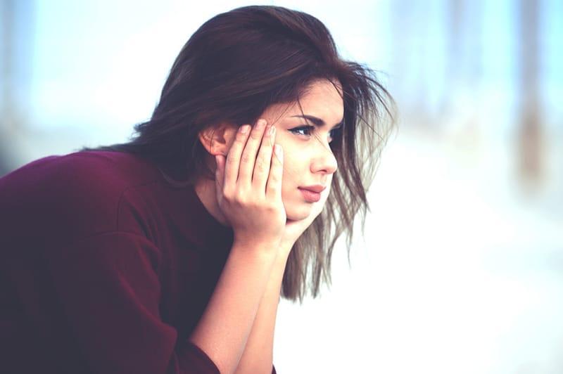 nachdenkliche Frau, die das Kinn auf ihre Handflächen stützt und weit weg schaut