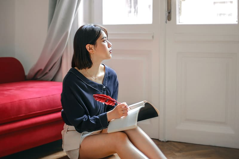 nachdenkliche Frau, die in einem Notizbuch schreibt, während sie zu Hause auf dem Boden sitzt