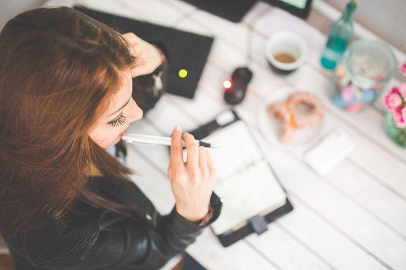 nachdenkliche Frau hält einen Stift am Schreibtisch sitzend
