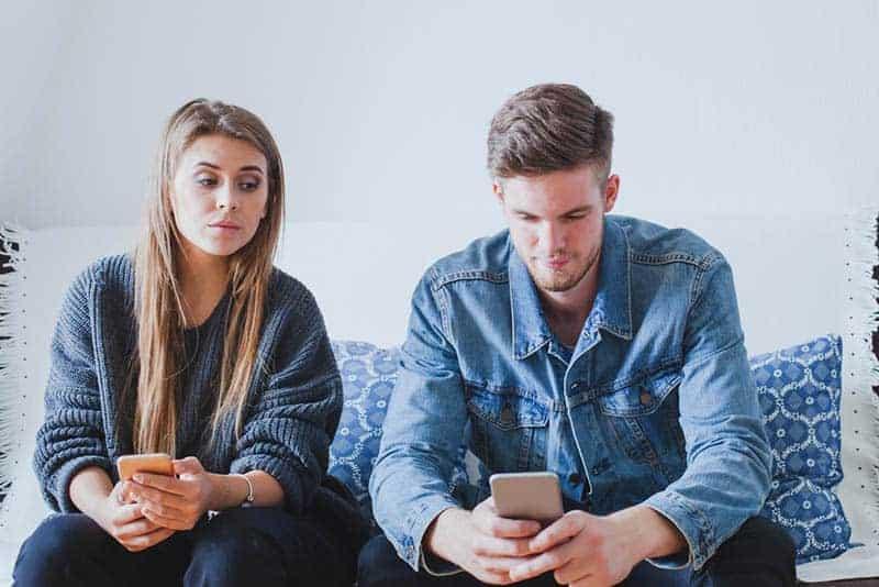 neugierige Frau, die auf das Telefon ihres Freundes schaut