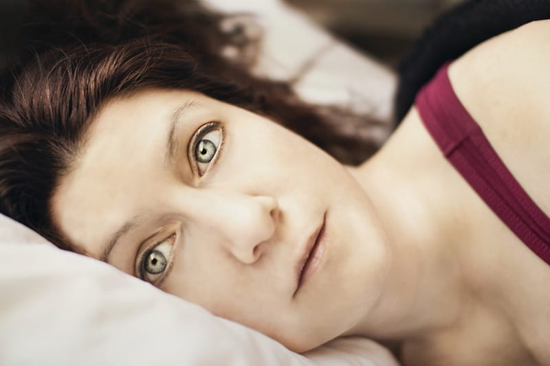 schlaflose Frau im Bett liegend mit offenen Augen