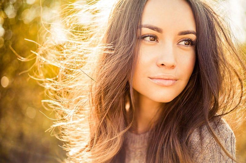 schöne Frau, die im Sonnenlicht steht