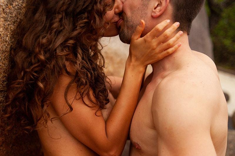 topless Paar küsst sich beim Anlehnen an die Wand
