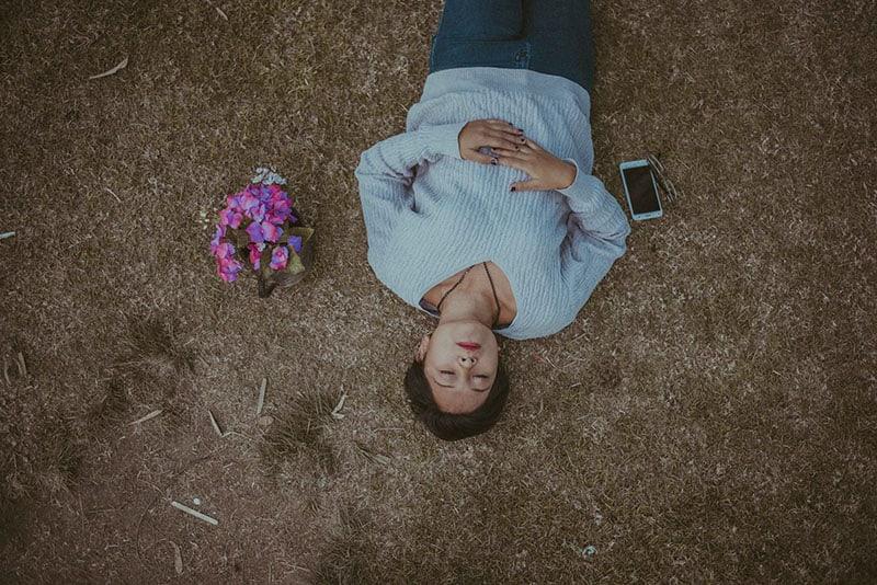 traurige Frau, die auf dem Boden mit Blumen und Handy liegt