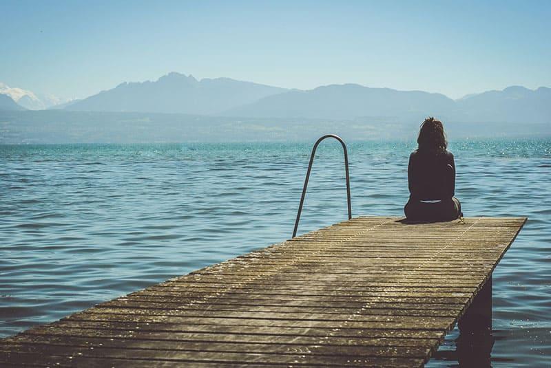 traurige Frau, die auf dem Pier sitzt