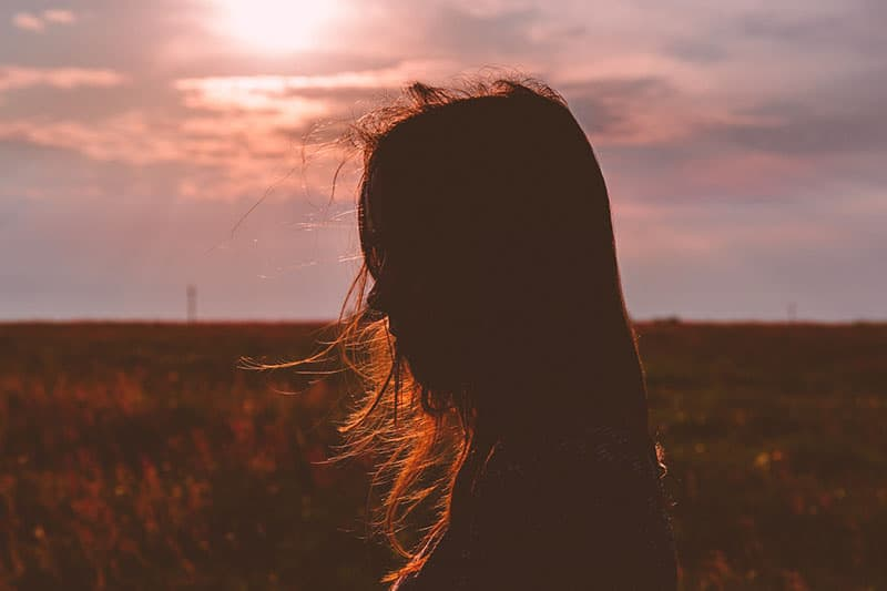traurige Frau, die auf der Wiese im Sonnenlicht steht