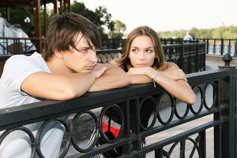 traurige Frau, die ihren nachdenklichen Freund ansieht, während beide sich auf den Zaun lehnen