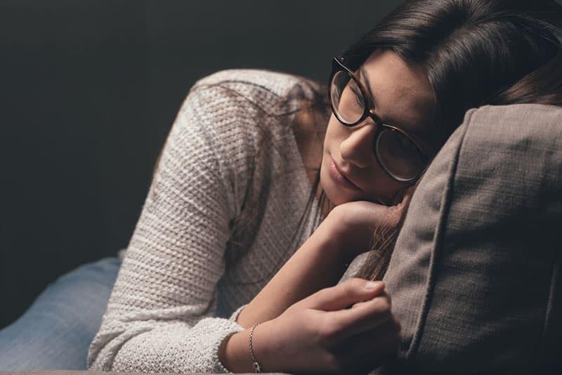 traurige Frau mit Brille, die Entfernung betrachtet