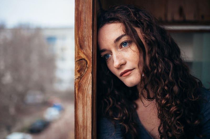 traurige Frau mit blauen Augen, die Entfernung betrachten