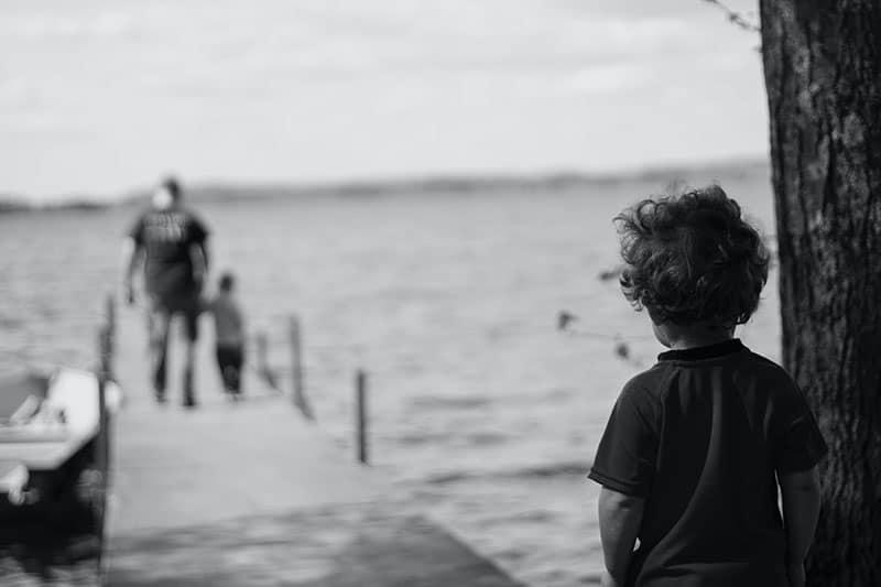 trauriger kleiner Junge, der Vater und seinen Sohn ansieht