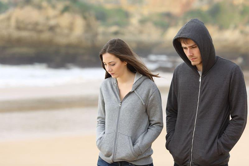 trauriges junges Paar, das auf dem Strand geht