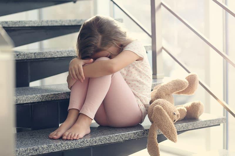 trauriges kleines Mädchen, das auf der Treppe sitzt