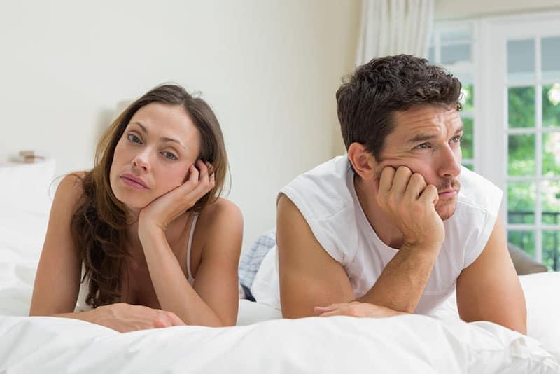 unglückliches Paar auf dem Bett liegen