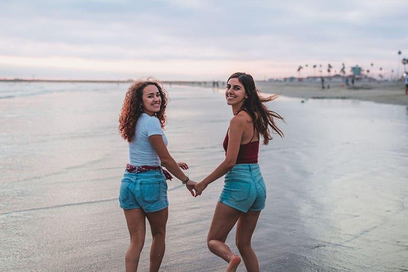 zwei Frauen Händchen haltend am Strand