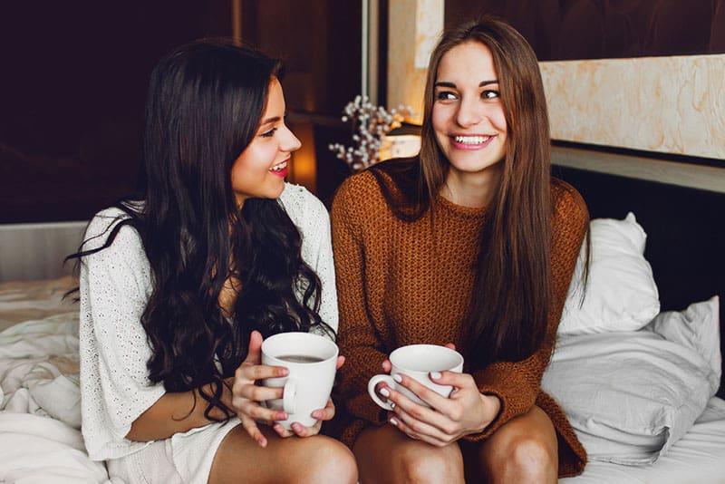 zwei Frauen sitzen auf dem Bett und reden