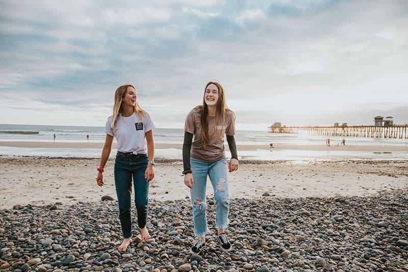 zwei Freunde, die am Strand lächeln
