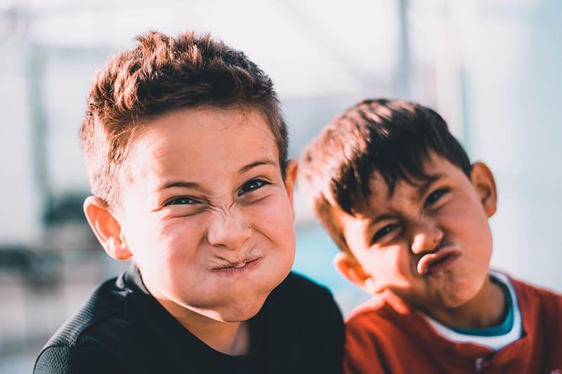 zwei Jungen, die verrückte Gesichter machen, während sie nebeneinander stehen