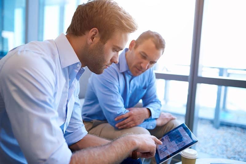 zwei Männer sitzen und betrachten Tablette