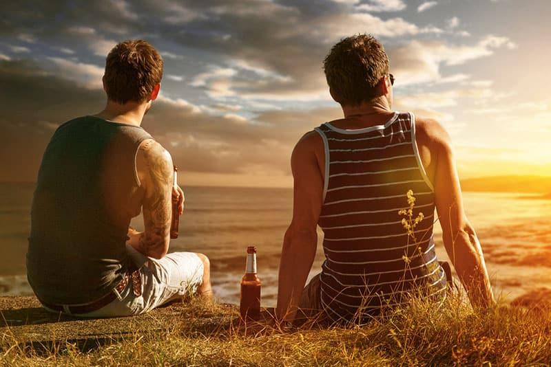 zwei beste Freunde sitzen in der Natur und trinken Bier