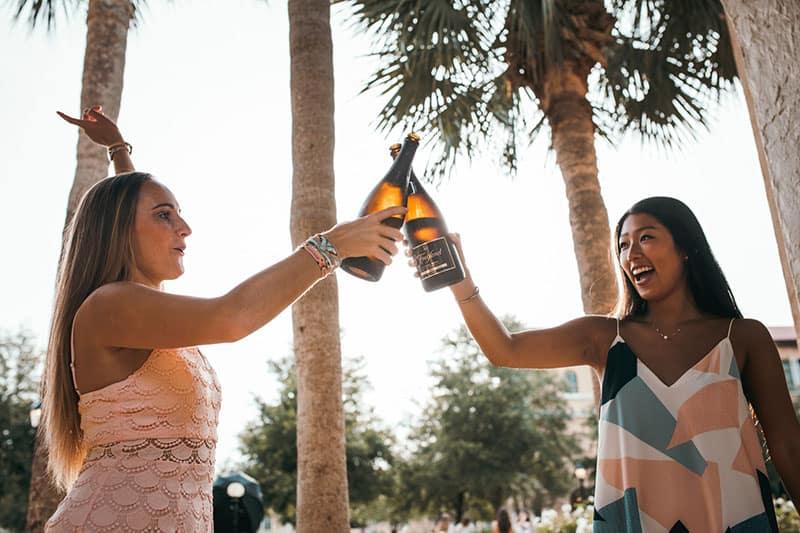 zwei junge Frauen mit einer Flasche Champagner