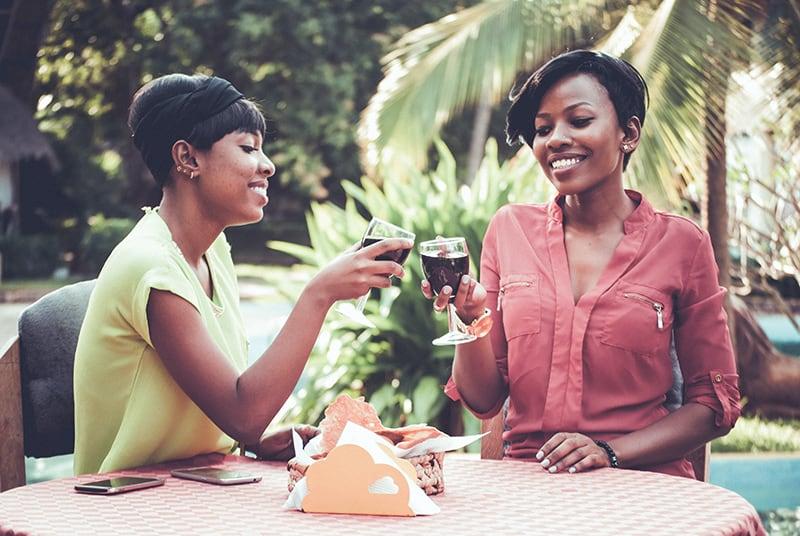 zwei lächelnde Freundinnen, die mit einem Glas Wein anstoßen, während sie in einem Straßencafé sitzen