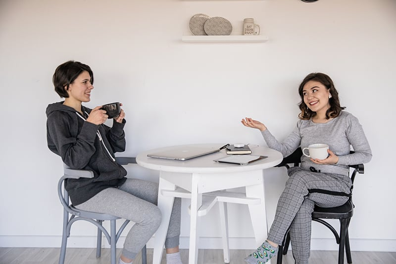 zwei lächelnde Freundinnen, die sprechen, während sie zusammen Kaffee am Tisch trinken