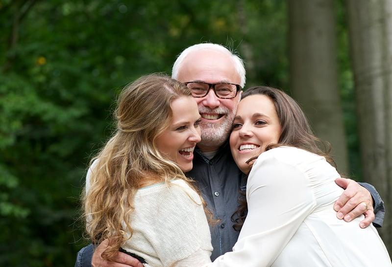 zwei lächelnde Töchter umarmen ihren Vater, während sie im Garten stehen